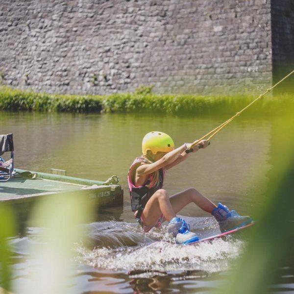 Olle hjälper en tjej prova på wakeboard