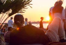 En kille njuter av solnedgången på Surfers Corner